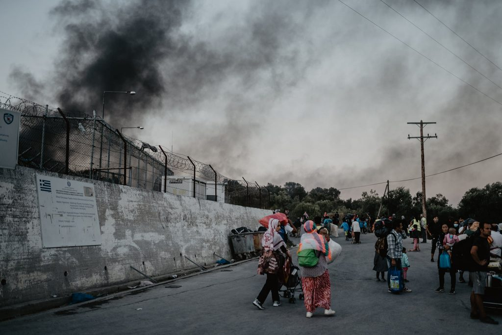 Black smoke over the walls of Camp Moria, parents and children evacuated outside.