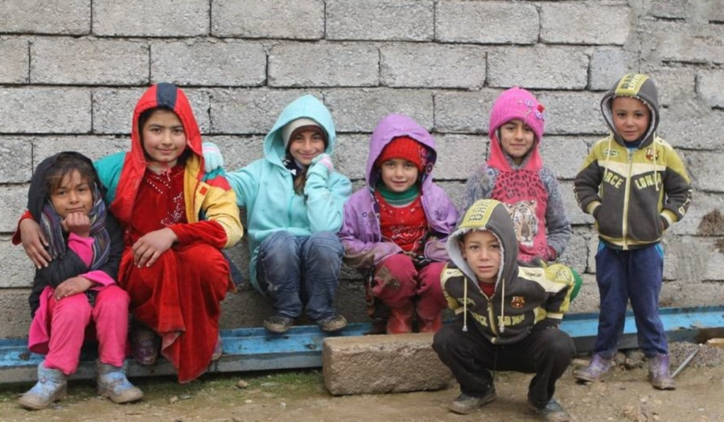 Children smiling at the camera in Moira camp