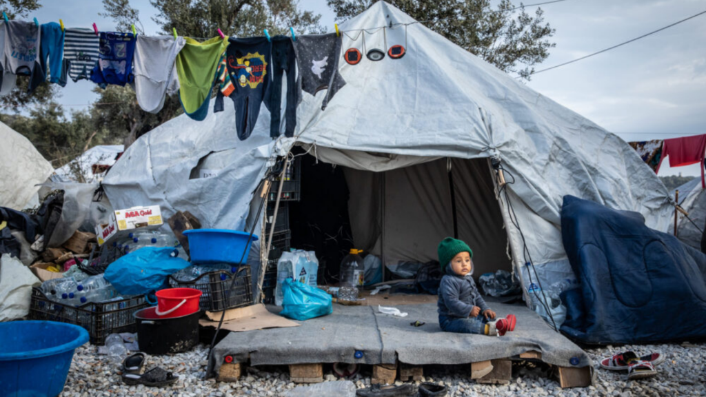 Child sitting in front of tent in Greece