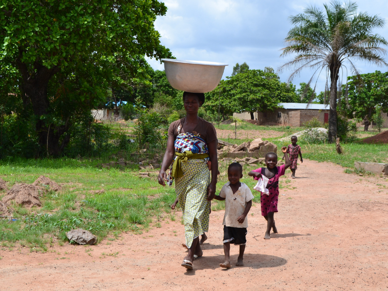 Woman with bucket of water on head walking with children