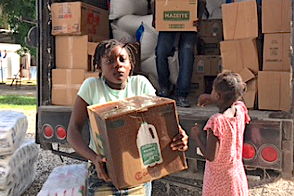 girl receiving a box of donations from distribution